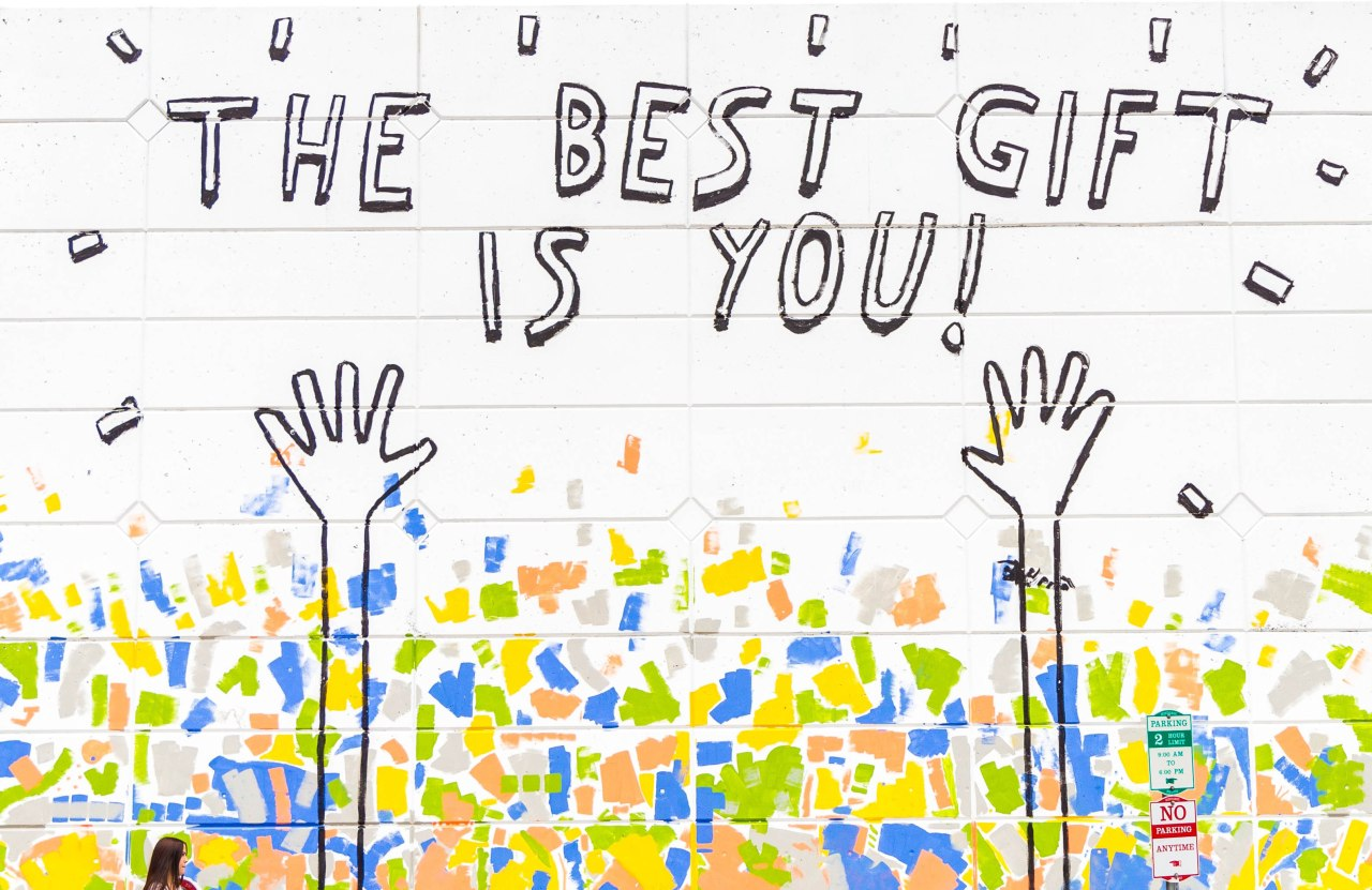 An image of a mural with raised hands that reads, 'The best gift is you!'