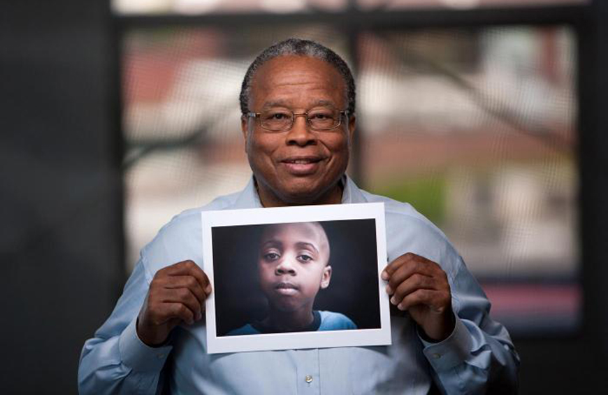 Image of a Court Appointed Special Advocate holding photo of young boy